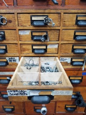To overcome labeling problems that arise from the language barriers within the workshop, Rueckenwind volunteers attached example bike parts to the drawers where parts are stored. Photo by Alicia Leggett