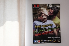 "A poster on Sally's wall shows two men kissing, with ""Love Deserves Respect"" written in Arabic, German and Turkish. Living in the LGBTQ camp has made it possible for Sally to openly express her sexuality and atheistic views without fear of discrimination or isolation. Photo by Lucy Tompkins"